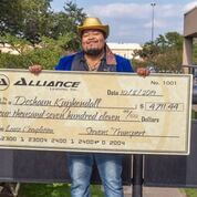 Image of Deshawn Kuykendall holding a large check for $4711.44